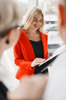 Dealer samochodowy uśmiecha się i stoi obok klienta. portret kobiety