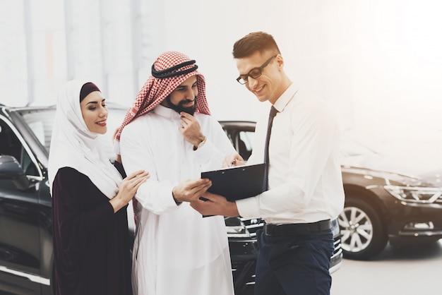 Dealer sprzedaje samochód bogaty arabski klient czyta umowę.