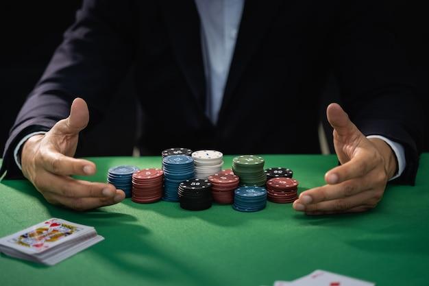 Dealer z kartami do pokera i żetonami w kasynie