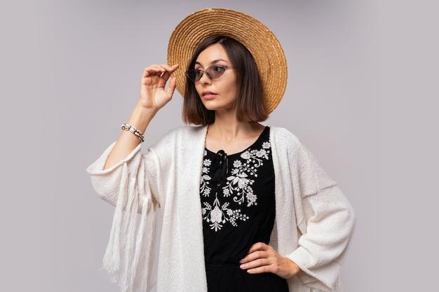 Debonair ciemnooka dziewczyna w słomkowym kapeluszu i letnim stroju boho pozuje.