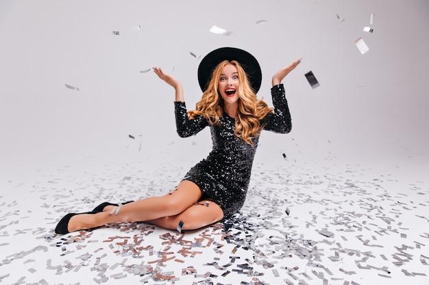Debonair kaukaski dziewczyna pozuje po imprezie z uśmiechem. zainspirowana długowłosa kobieta siedzi na białej ścianie z konfetti.