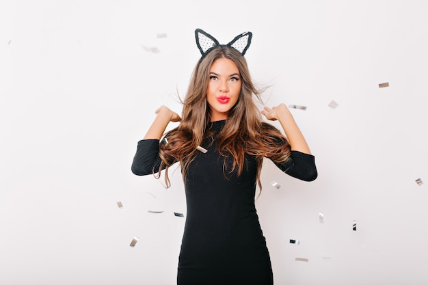 Debonair kobieta pozuje pod konfetti w studio