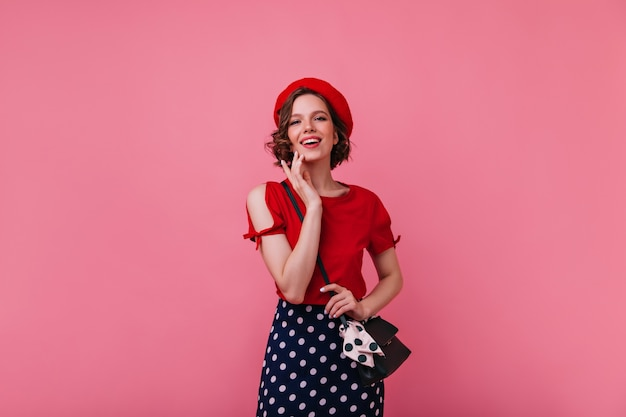 Debonair kobieta w wiosennym francuskim stroju podczas sesji zdjęciowej. portret kaukaski dziewczyna w berecie z uśmiechem.