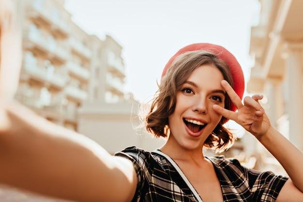 Debonair kobieta we francuskim berecie pozuje na ulicy ze znakiem pokoju. plenerowe zdjęcie czarującej dziewczyny o ciemnych oczach.