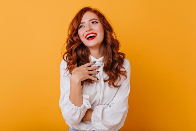 Debonair kobieta z falującą fryzurą, śmiejąc się na żółtej ścianie. kryty fotografia wdzięcznej rudej pani w białej bluzce.