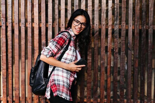 Debonair opalona dama w okularach bawiąca się podczas sesji zdjęciowej. plenerowe zdjęcie wspaniałej dziewczyny z modnym plecakiem stojącym na drewnianej ścianie.