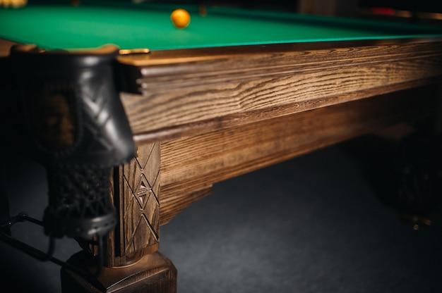 Dębowa ozdobna noga stołu bilardowego wygląda na kosztowną.