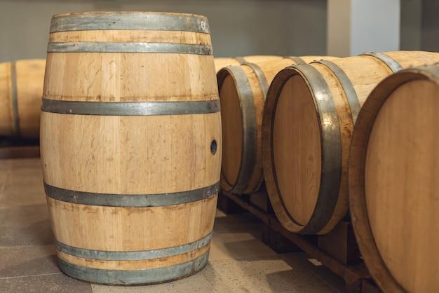 Dębowe beczki z winem, w których dojrzewa czerwone wino w piwnicy winnicy.