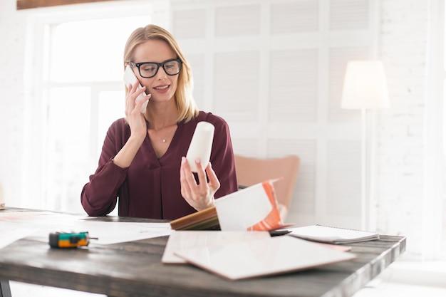Decyzja wewnętrzna. wątpliwa projektantka niosąca plafon podczas rozmowy przez telefon