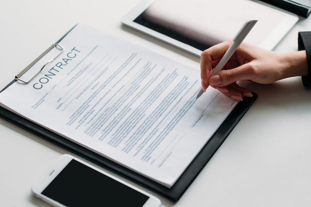 Decyzja wykonawcza. biznesowa kobieta zawiera umowę z partnerami. zbliżenie kobiece strony podpisywania umowy.