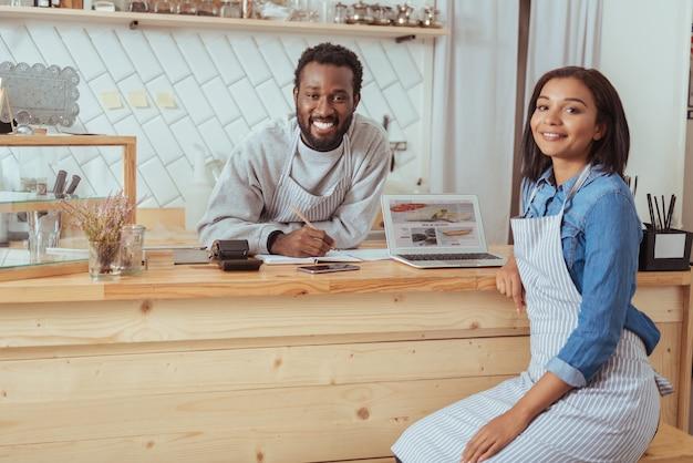 Dedykowani pracownicy. przyjemni młodzi bariści siedzący przy ladzie i uśmiechający się do kamery, omawiając i sugerując ulepszenia strony internetowej swojej kawiarni