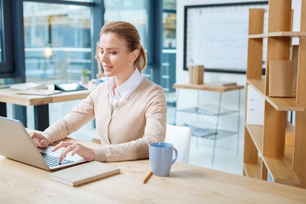 Dedykowany do pracy. uśmiechnięty kierownik biura pracujący z laptopem, patrząc na ekran i wyrażający optymizm