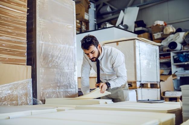 Dedykowany pracowity brodaty inżynier stojący w magazynie i liczący arkusze.