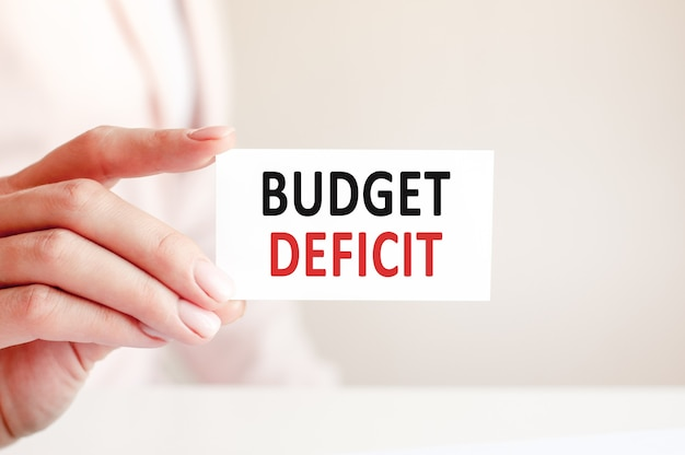 Deficyt budżetowy jest zapisany na białej wizytówce ręką kobiety.