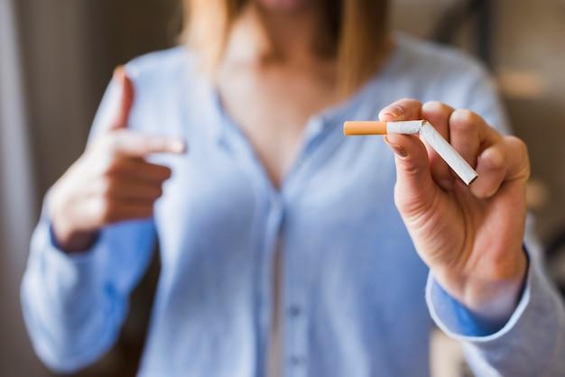 Defocus kobieta wskazuje przy łamanym papierosem