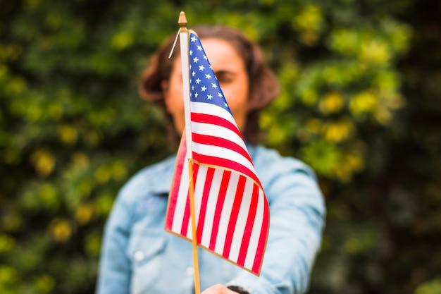 Defocused kobieta trzyma usa amerykańską flaga przed jej twarzą