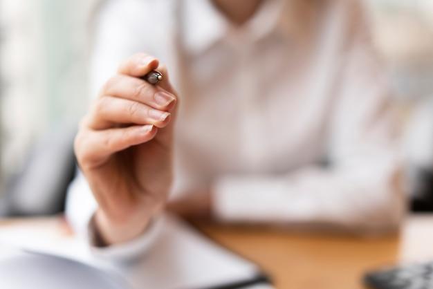 Defocused kobieta wskazuje pióra zakończenie up