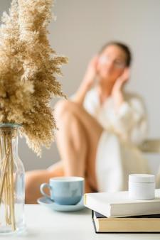 Defocused kobieta z łatami do oczu cieszy się kawę w domu