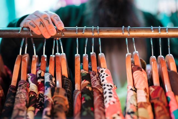 Defocused mężczyzna wybiera koszula wiesza na poręczu w sklepie