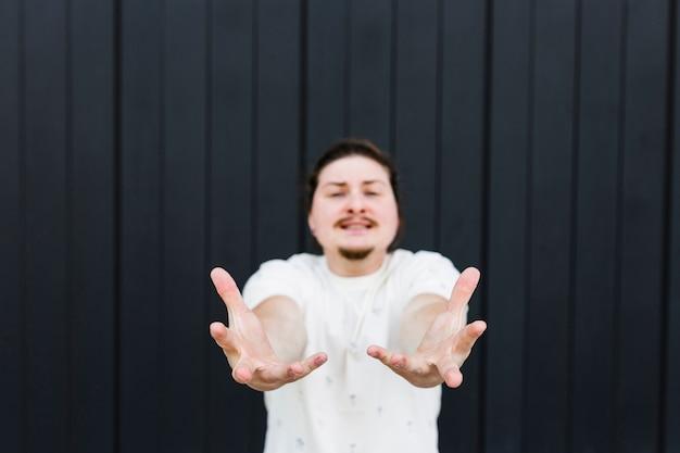 Defocused młody człowiek robi ręka gestowi przeciw czarnej pasiastej ścianie