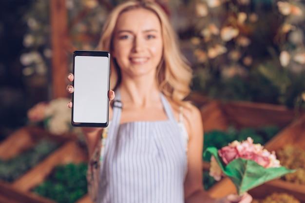 Defocused żeński kwiaciarni mienia kwiat w ręce pokazuje mądrze telefon z białym parawanowym pokazem