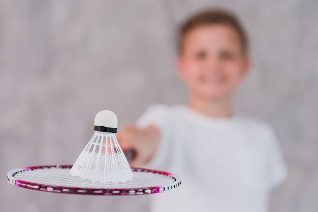 Defocussed chłopiec trzyma wolant na rakiecie przeciw szarej ścianie