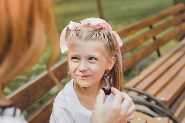 Degustacja cukierków. niebieskooka śliczna dziewczyna z piękną fryzurą smakującą słodkich cukierków w parku
