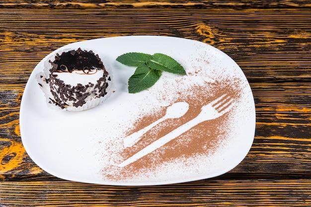 Dekadencki deser pokryty wiórkami czekoladowymi pod dużym kątem i podany na talerzu z dekoracją z liści mięty i konturami naczynia posypany kakao i spoczywający na drewnianej powierzchni stołu