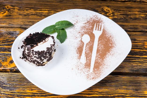Dekadencki deser pokryty wiórkami czekoladowymi pod dużym kątem i podany na talerzu z dekoracją z liści mięty i konturami naczynia posypany kakao i spoczywający na powierzchni drewnianego stołu