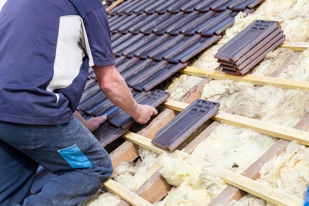 Dekarz kładzie dachówkę na dachu