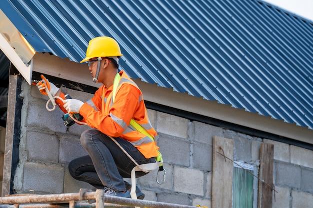 Dekarz ma na sobie pasy bezpieczeństwa podczas pracy przy konstrukcji dachu budynku na placu budowy.