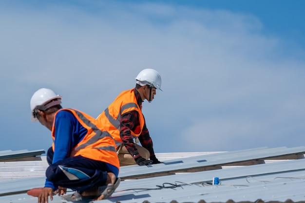 Dekarz pracownik w mundurze ochronnym i rękawice pracy instalacji blachy na szczycie nowego dachu na placu budowy.