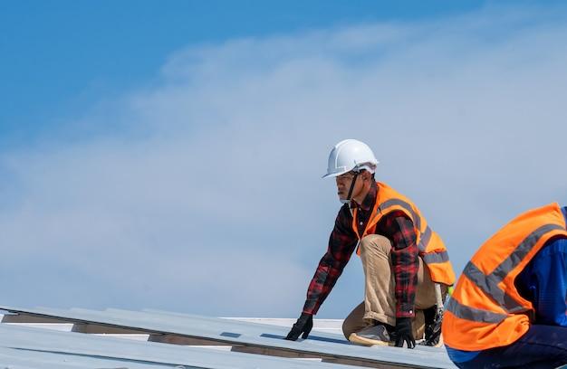 Dekarz pracownik w mundurze ochronnym instalowanie metalowego dachu na szczycie nowego dachu, koncepcja budynku mieszkalnego w budowie.