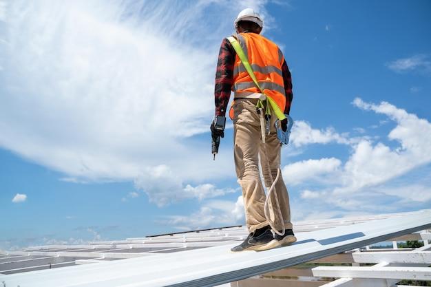 Dekarz pracujący przy montażu dachu z profili metalowych, narzędzia dekarskie, wiertarka elektryczna używana na nowych dachach.