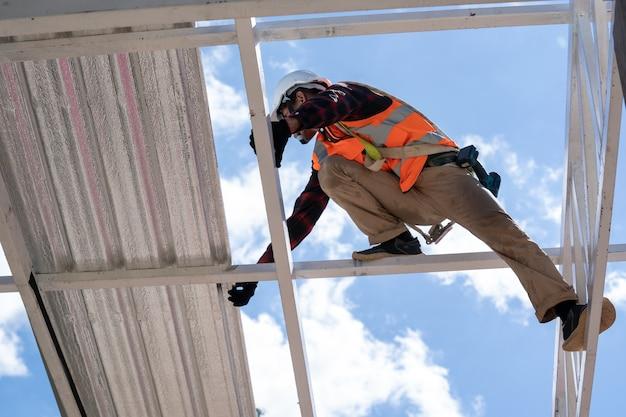Dekarz pracujący w ochronnych rękawicach roboczych, pracownik budowlany noszący szelki bezpieczeństwa pracujący na wysokim poziomie na placu budowy, montuje nowy dach, metalowy dach.