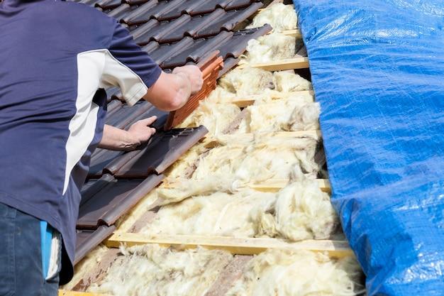 Dekarz układający dachówkę na dachu