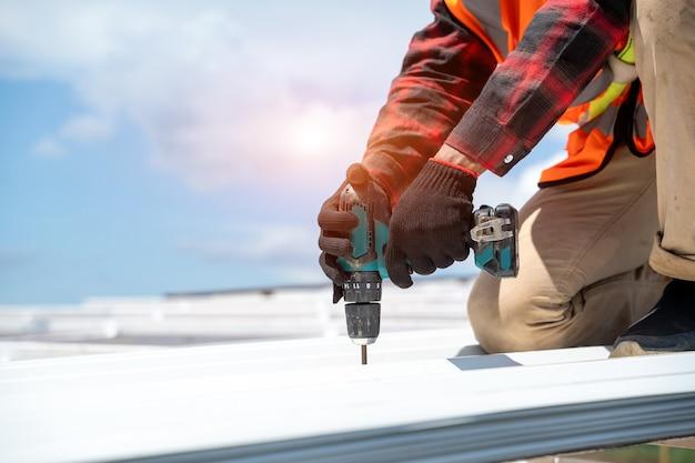 Dekarz w mundurze ochronnym i rękawicach, używając pneumatycznego lub pneumatycznego pistoletu do gwoździ i instalując metalowy dach na nowym dachu, koncepcja budynku mieszkalnego w budowie.