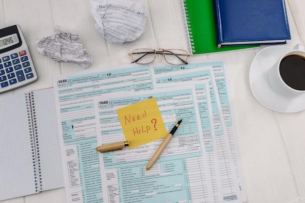 """Deklaracja podatkowa z tekstem """"potrzebuję pomocy"""" na stole"""