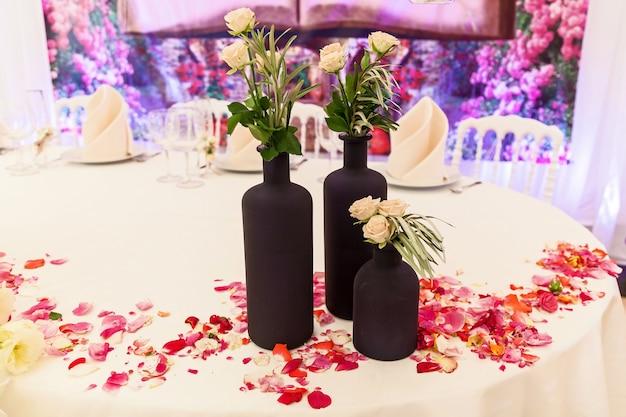 Dekor z czarnych butelek z kwiatami i płatkami róż na weselny stół eleganckie przyjęcie weselne