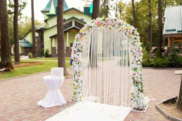 Dekoracja ceremonii ślubnej. biały łuk z koncepcją kwiatów. zbliżenie.