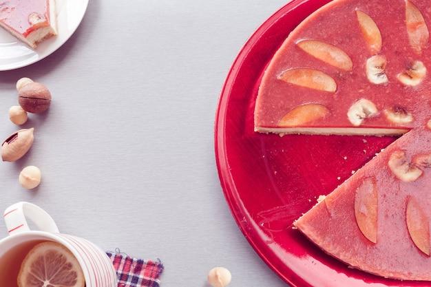 Dekoracja czerwonego sernika nektarynką z herbatą
