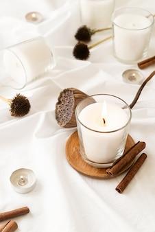 Dekoracja domu i wnętrza. piękne palące się świece z cynamonem i suchymi kwiatami na białej powierzchni tkaniny