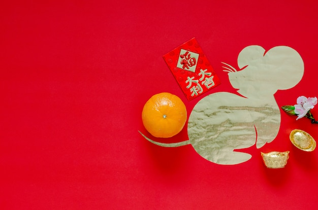 Dekoracja festiwalu chińskiego nowego roku na czerwonym tle, które wycięte w kształcie szczura nakłada na złoty papier.