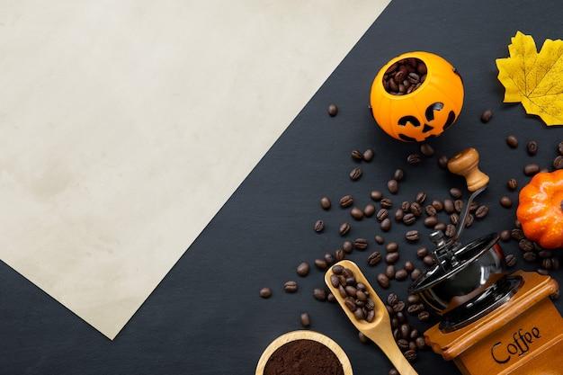 Dekoracja halloween z gorącą kawą i fasolą na ciemnym tle. leżał płasko. skopiuj miejsce na tekst.