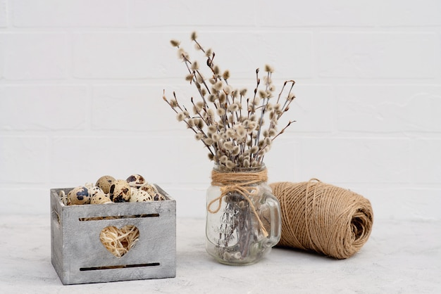 Dekoracja jaja ptasiego przepiórki w drewnianym koszu ze świeżymi gałązkami wierzby i bułką biczową.