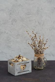 Dekoracja jajka przepiórczego w drewnianym koszu ze świeżymi gałązkami wierzby jutowej.