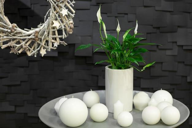 Dekoracja kulistej świecy i wazonu z kwiatem i wieńcem z gałązek na czarnym tle