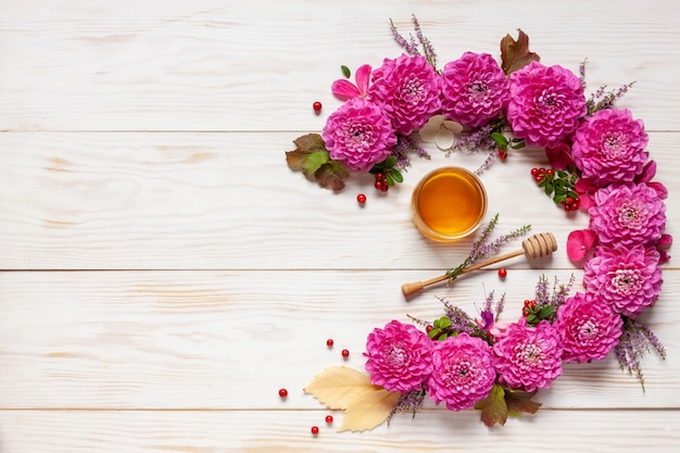 Dekoracja kwiatowa. z różowymi dahlijas, jesiennymi liśćmi, brusznicą i miodem