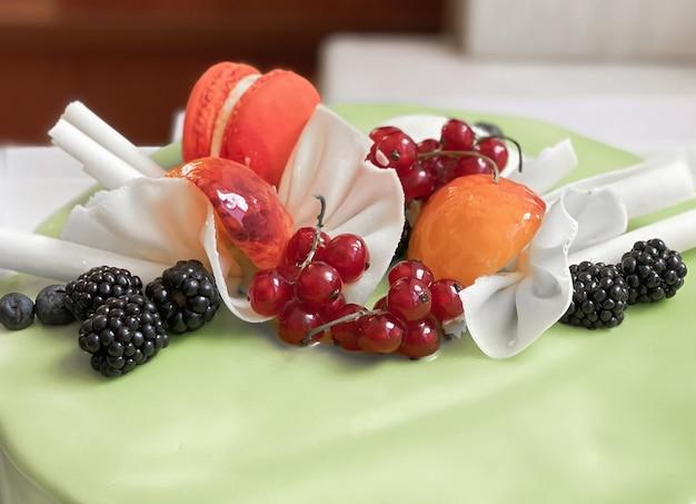 Dekoracja na jasnozielonym cieście w postaci świeżych owoców, porzeczek, jeżyn, jagód, makaroników z ciasta morelowego i pomarańczowego oraz paluszków z białej czekolady. wystrój ciasta.
