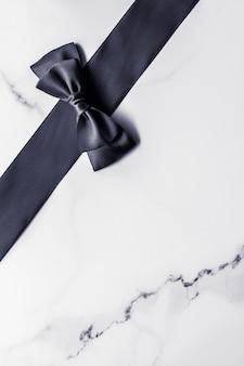 Dekoracja na prezent świąteczny i koncepcja promocji sprzedaży czarna jedwabna wstążka i kokardka na marmurowym tle f...